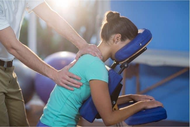 une femme qui reçoit un massage sur une chaise au travail